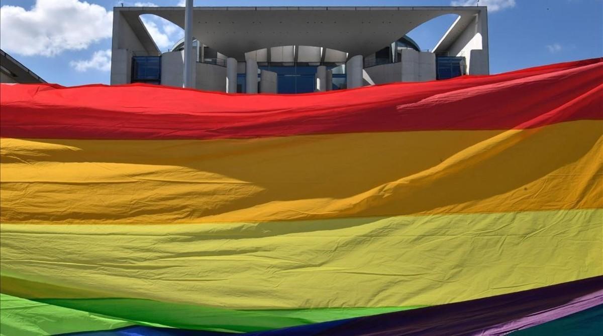 Unos activistas sostienen una bandera arcoiris frente al parlamento en Berlín.
