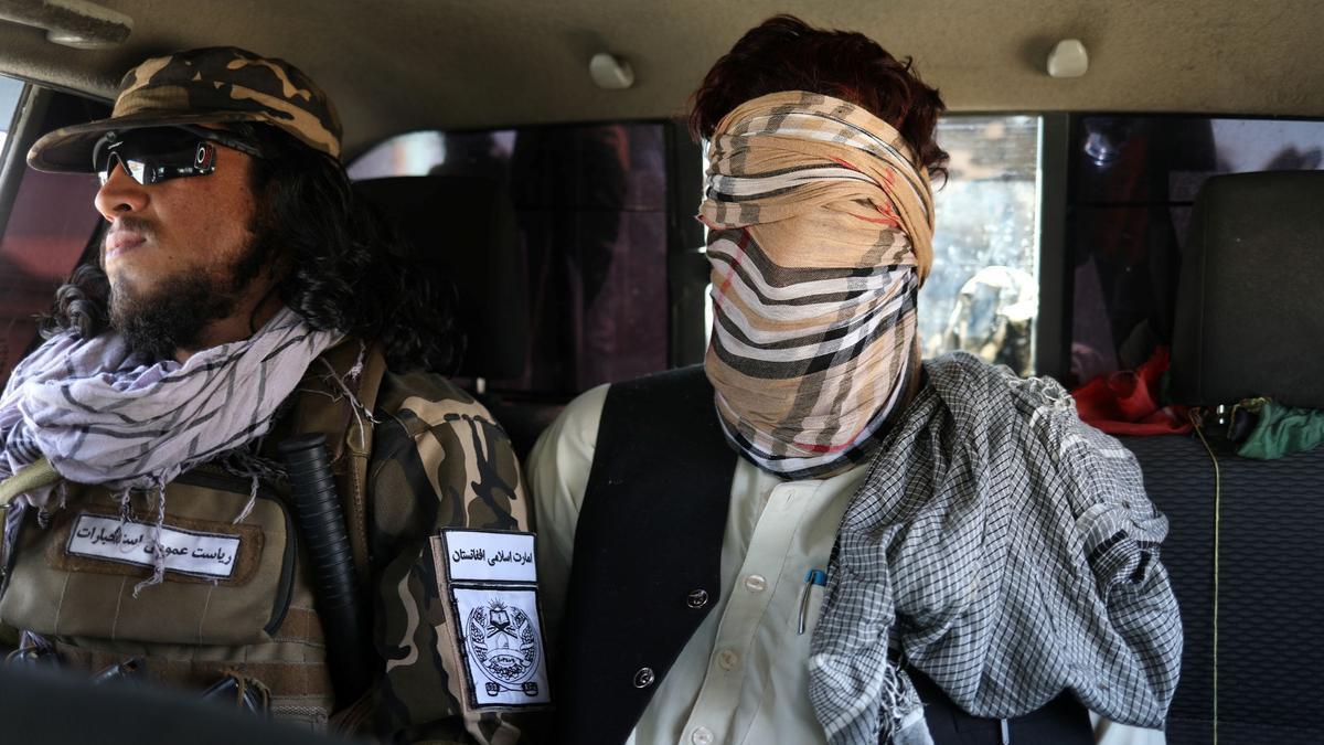 Un sospechoso de pertenecer al ISIS, con una venda en los ojos, junto a un miembro del ejército talibán en Kabul