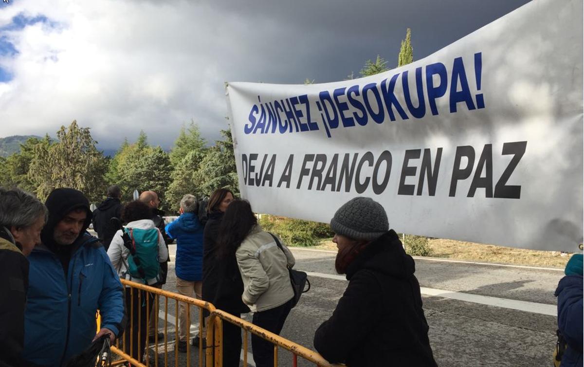 Un grupo de manifestantes instala una pancarta contra la exhumación de Francisco Franco a la puerta del Valle de los Caídos en la mañana del día en que se llevó a cabo, el 24 de octubre de 2019.
