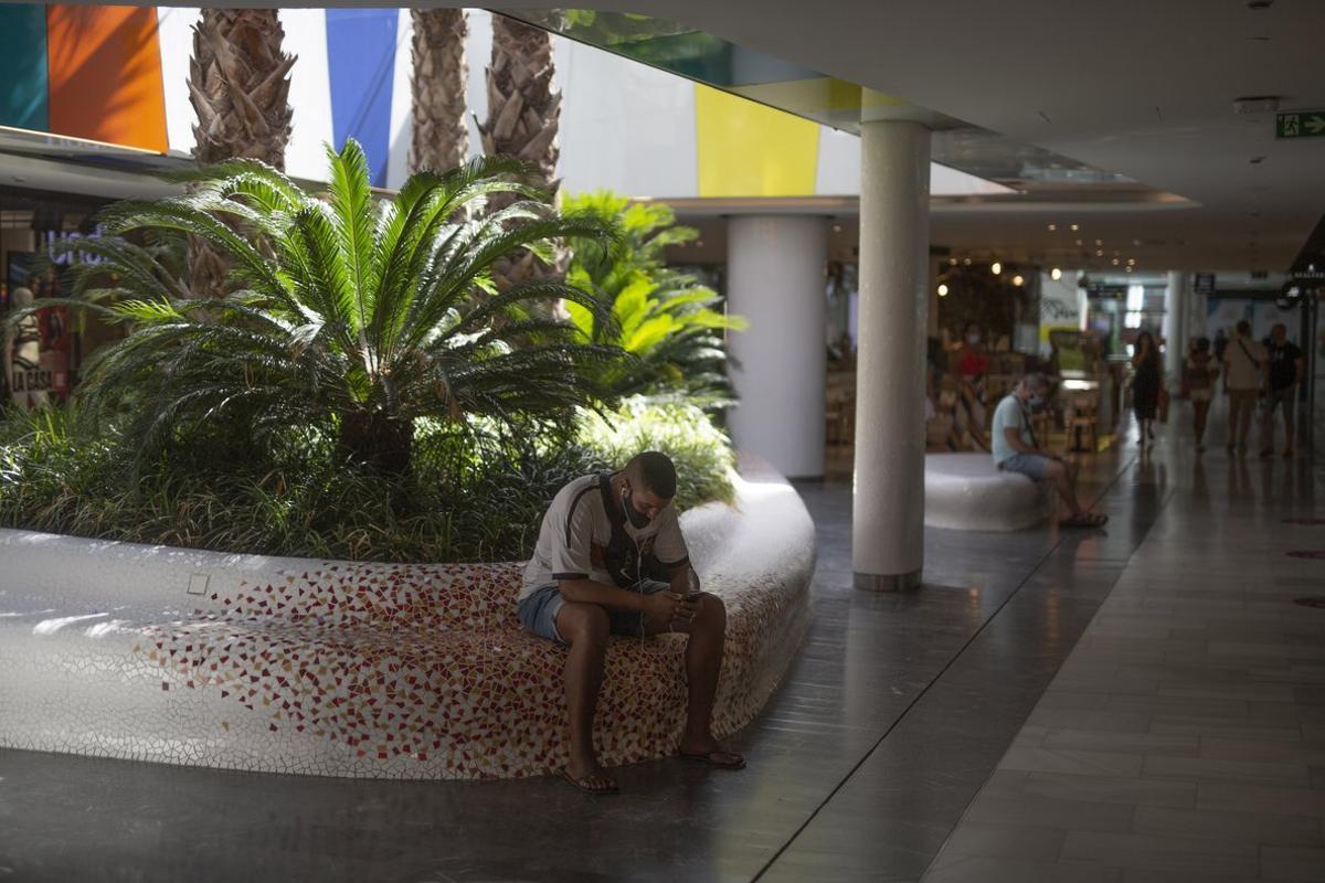 Gente sentada en los bancos del centro comercial Glòries