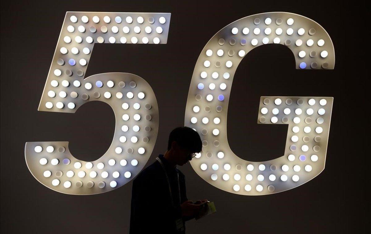 Un visitante usa su teléfono junto a un cartel de 5G.