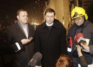 El primer ministro de Letonia, Valdis Dombrovskis (centro), y el ministro de Interior, Rihards Kozlovskis, visitan el lugar del derrumbe del centro comercial, el pasado 21 de noviembre en Riga.