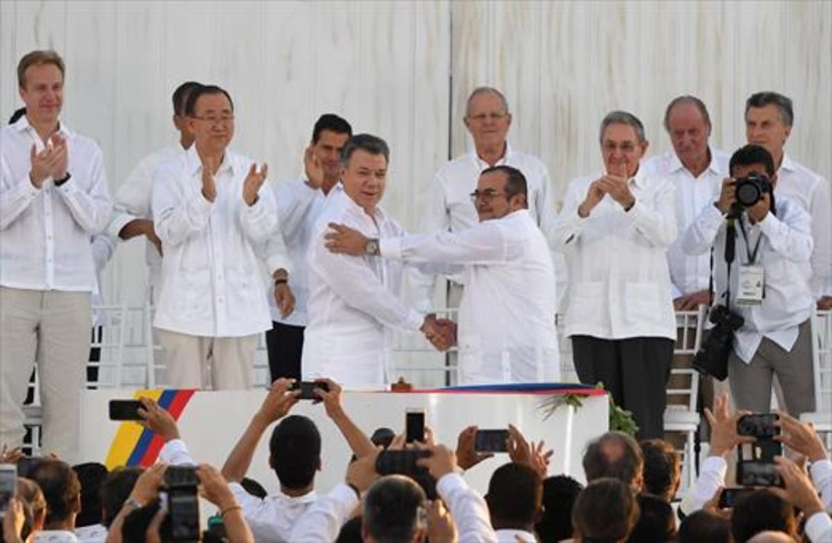 Santos y Timochenko se dan la mano entre los aplausos de Ki-mon,Castro y el rey emérito Juan Carlos, entre otras personalidades.
