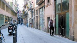 Un hombre pasa ante la puerta de un hostal ya cerrado en la calle D'en Roig, ayer.