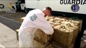 Un agente de la Guardia Civil con parte de las seis toneladas de drogas intervenidas a una banda de narcos que operaba entre Málaga y Francia.