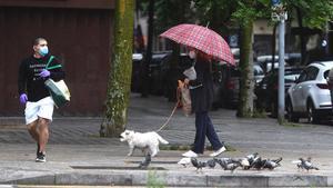 Dos transeúntes bajo la lluvia, en Barcelona.