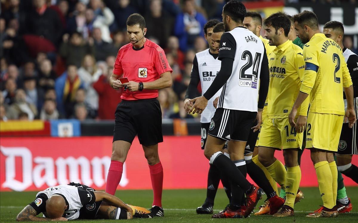 El árbitro del Valencia-Villarreal se dirige a mostrar la segunda amarilla a Zaza, en el suelo.