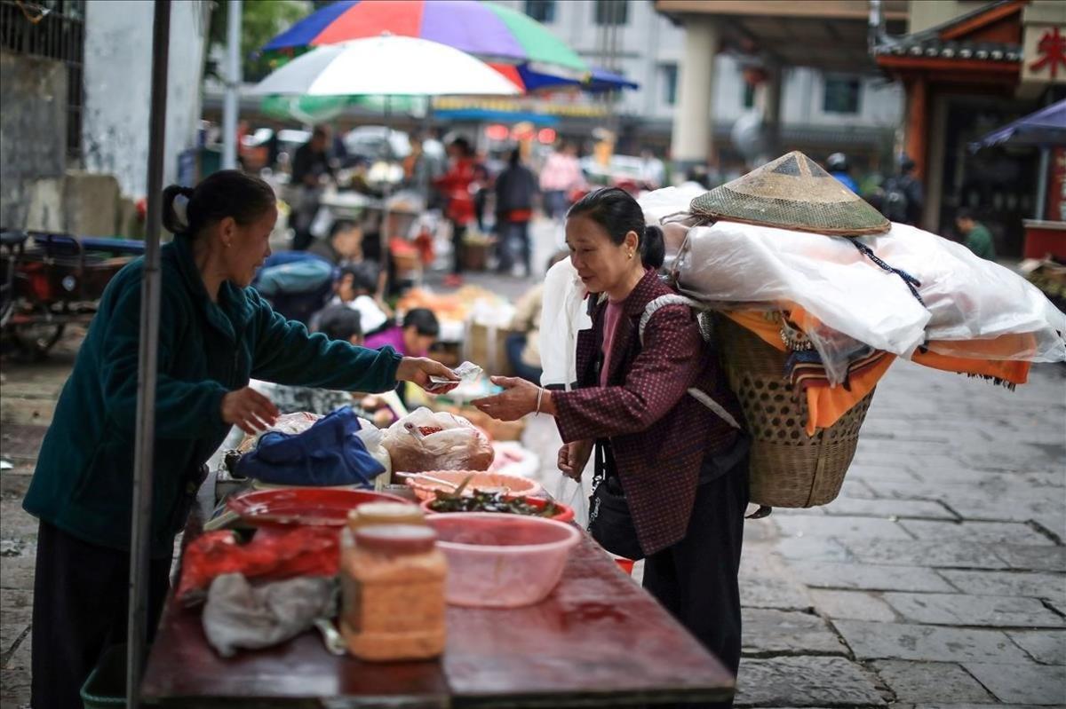 Una mujer compra en un mercado de Xiangxi, en la provincia de Hunan.
