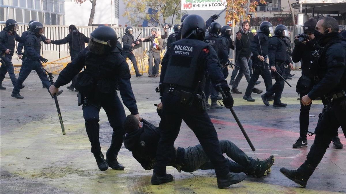 Dos mossos arrastran a un manifestante en la plaza del 1 d'Octubre de Girona