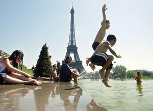 Niños saltando y bañándose en frente de la Torre Eiffel, en París.
