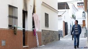 Un hombre pasa por delante de la vivienda donde se registró el incendio en la madrugada de este domingo.