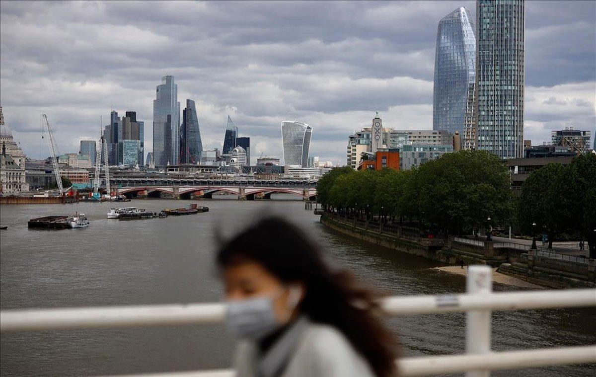 Una peaton cruza el puente de Waterloo, sobre el Támesis, con la City al fondo.