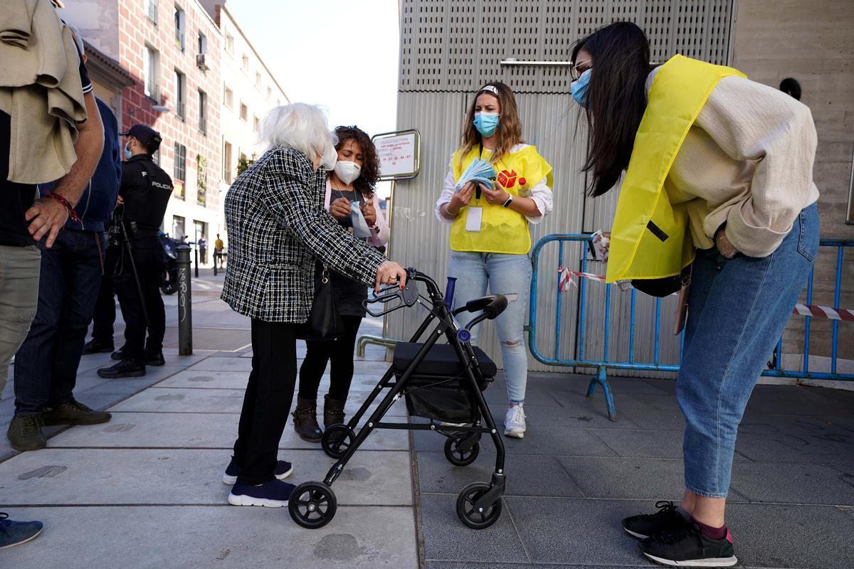 Ambiente electoral en el barrio deChueca , unas enfermeras a la entrada de un colegio electoral dan mascarillas y gel para cumplir las normas anti Covid.