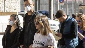 Personas con mascarilla ante el riesgo de coronavirus hacen cola ante la oficina del padrón del Ayuntamiento de Valencia.