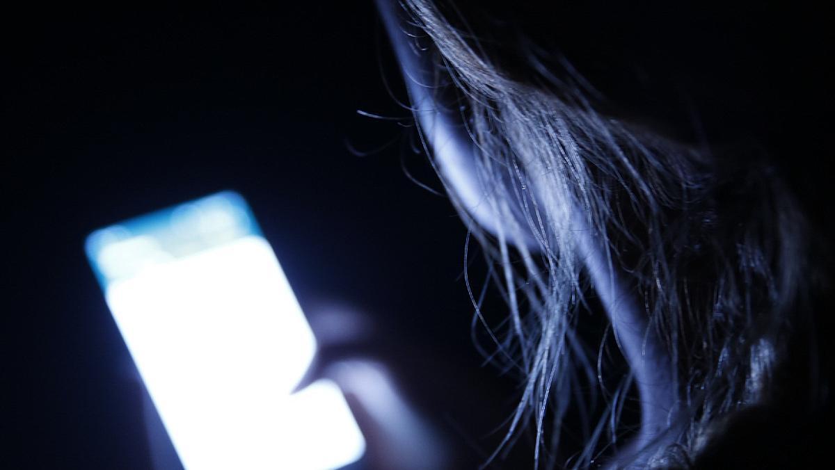 Una mujer mira su móvil.
