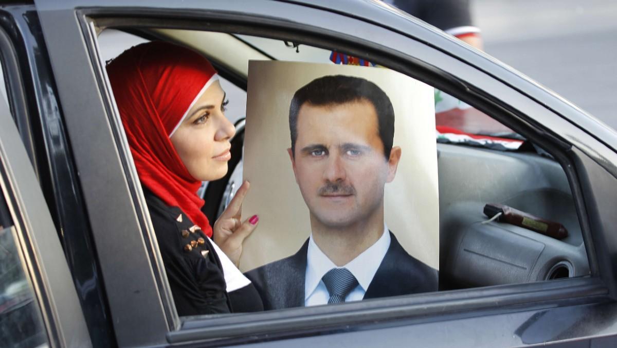 Una mujer muestra el retrato de Bashar a-Asad en una celebración del aniversario del presidente sirio, en Damasco, en el 2013.
