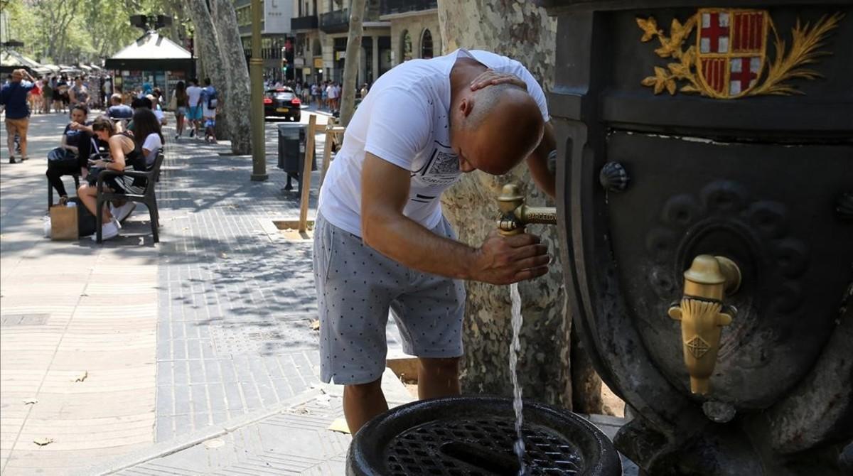 Un turista se refresca en la fuente de Canaletes, en la Rambla de Barcelona.