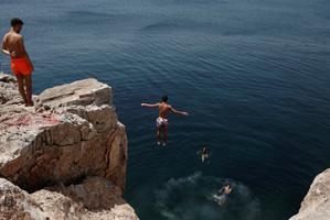 Un hombre se sumerge en el mar durante la ola de calor en Varkiza, cerca de Atenas.