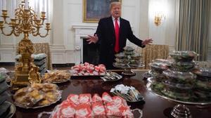 Trump ante las hamburguesas que encargó para recibir a un equipo de fútbol americano.