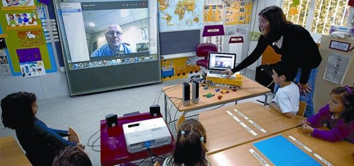 ACTIVIDAD 3 A la izquierda, niños de P-4 del CEIP Sant Martí muestran un transbordador de papel que les regaló la científica Alina Hirschmann. Ahora se turnan para llevárselo a casa. Arriba, la maestra Esther Manchón ayuda a un alumno a lanzar un cohete. A la derecha,  el astrofísico Serguei Odintsov conversa con los niños en una videoconferencia con la ayuda de su colega Hirschmann.