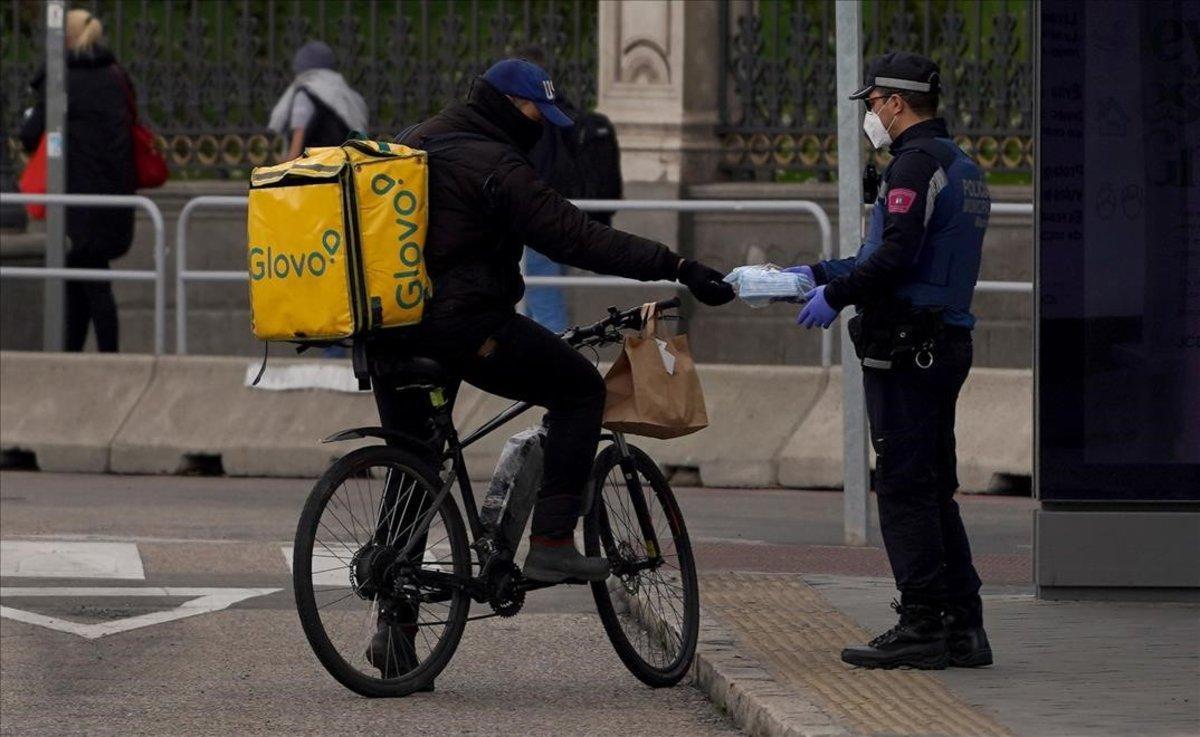 Un policía entrega una mascarilla a un repartidor de Glovo.