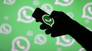 La silueta de un brazo sostiene un teléfono con el logo de WhatsApp.