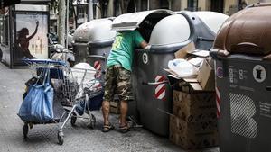Un hombre busca en unos contenedores en el Eixample de Barcelona.