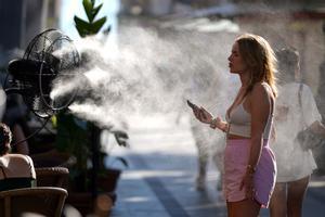 Peatones de la Gran Vía se refrescan causa del calor hoy en Madrid con un ventilador que expulsa agua.