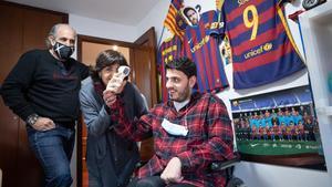 Pol Otero Arús, en su habitación plagada de fotografías del Barça, junto a sus padres Montse y Carlos.