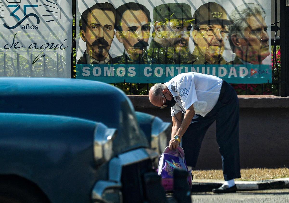 Un hombre con su coche frente al cartel del Partido Comunista cubano.