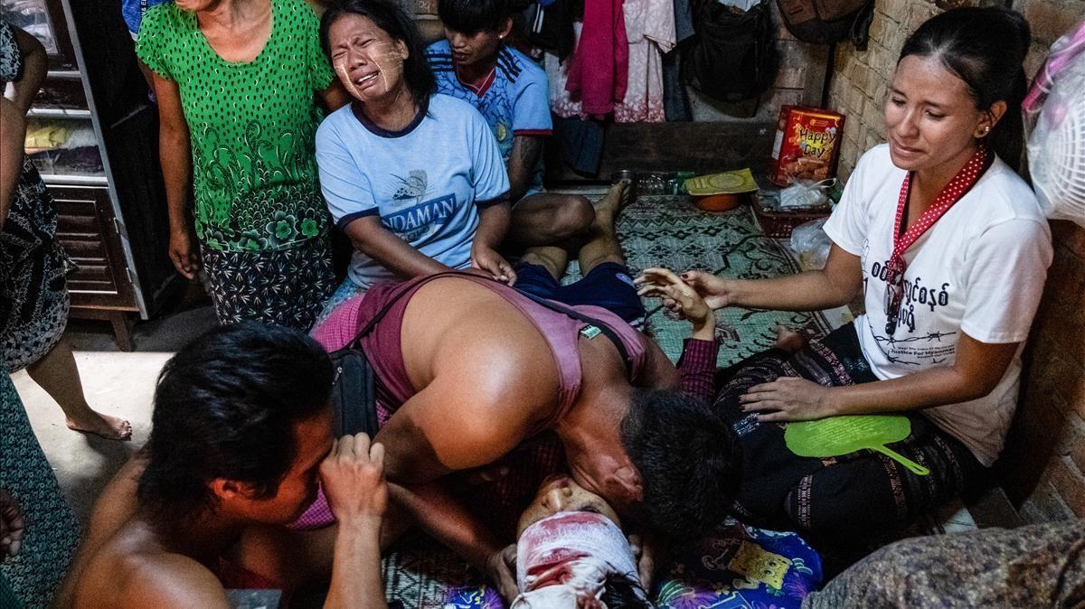 La familia de un fallecido por el disparo de los militares birmanos llora su pérdida en Rangún (Birmania)