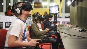 Unos adolescentes juegan a videojuegos en 3D en una feria de Barcelona.