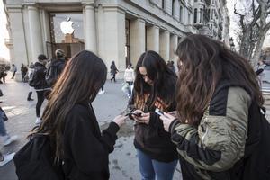 Unas jóvenes usan su smartphone delante de una tienda Apple en Barcelona.