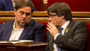 El 'exvicepresident' Oriol Junqueras y el 'expresident' Carles Puigdemont, en el hemiciclo del Parlament, en una foto de archivo del 2017.