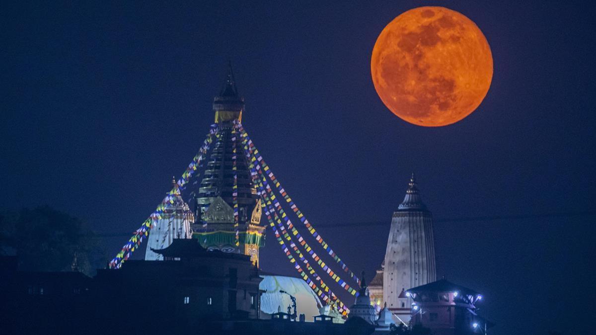 La superluna rosa se alza sobre Swayambhunath, el antiguo complejo religioso del valle de Katmandú, este martes.