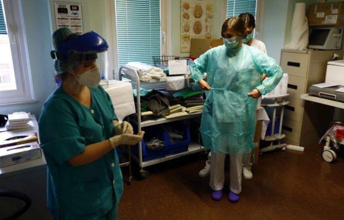 Una sanitaria ayuda a otra compañera a protegerse con el equipo, en el Servet.