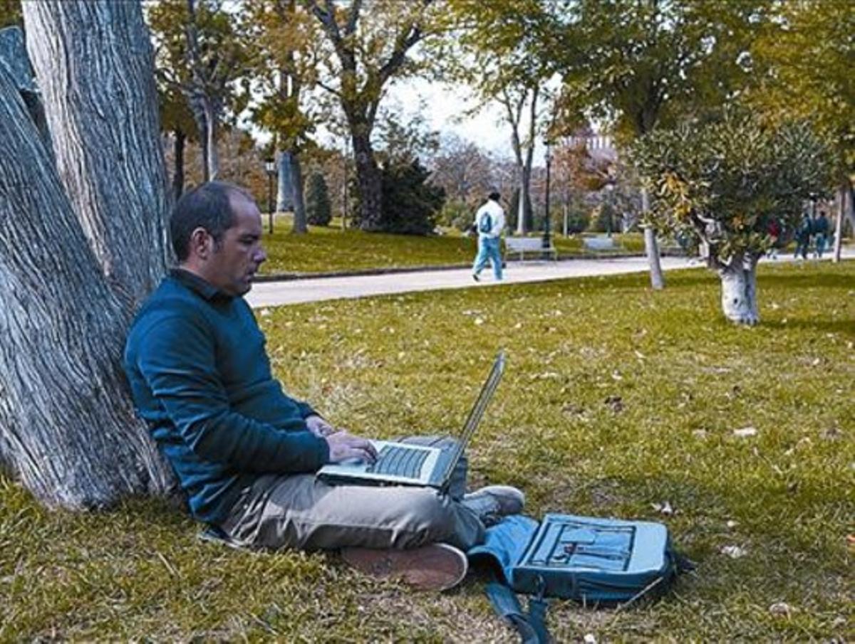 Un usuario utiliza el wifi público en el parque de la Ciutadella.
