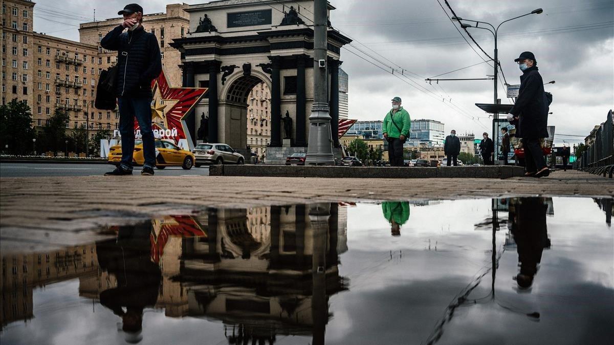 Personas con máscaras esperan en una parada de autobús cerca de Hero city, en Moscú