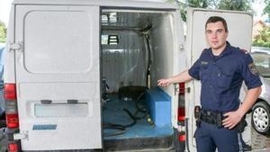 Un policía austríaco muestra la furgoneta donde iban los refugiados.