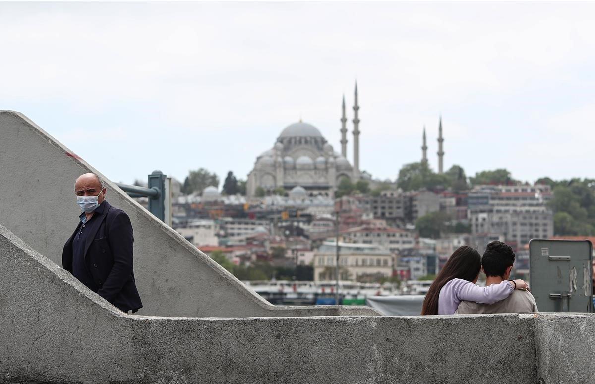 Una pareja sentada en una terrazafrente a la Mezquita de Suleymaniye.