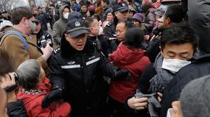 Un oficial de policía empuja a los manifestantes congregados frente al tribunal en el que era juzgado Pu Zhiqiang.