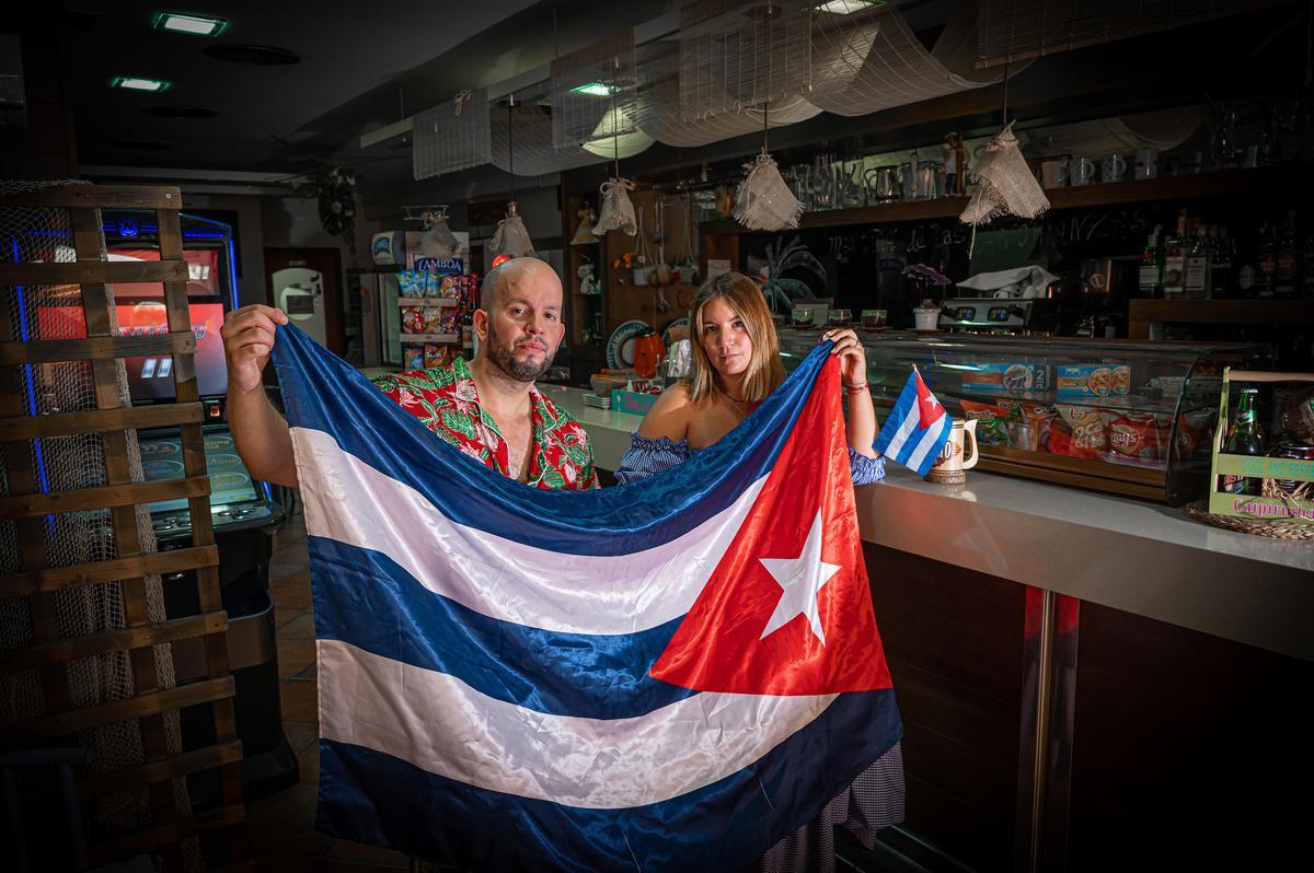 Riki y su hermana María posan con la bandera cubana en el restaurante familiar.