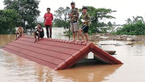 Un grupo de personas aguarda en lo alto de un tejado en una zona inundada en Laos.
