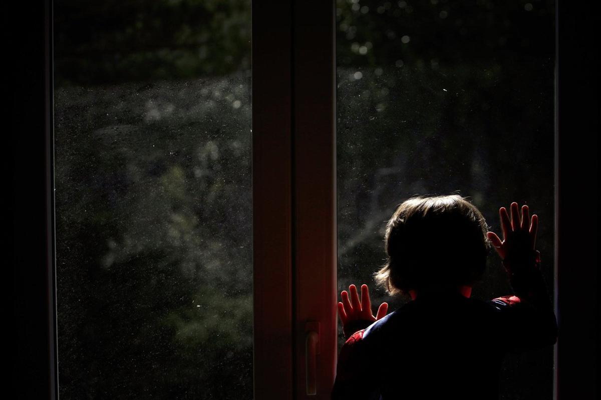 Un niño mira a la calle mientras permanece confinado por el coronavirus en A Coruña.