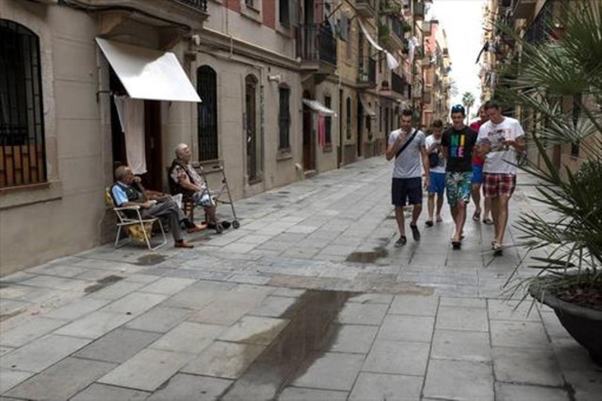 Dos vecinos tomando la fresca en la calle, símbolo del barrio, observan pasar a un grupo de turistas.