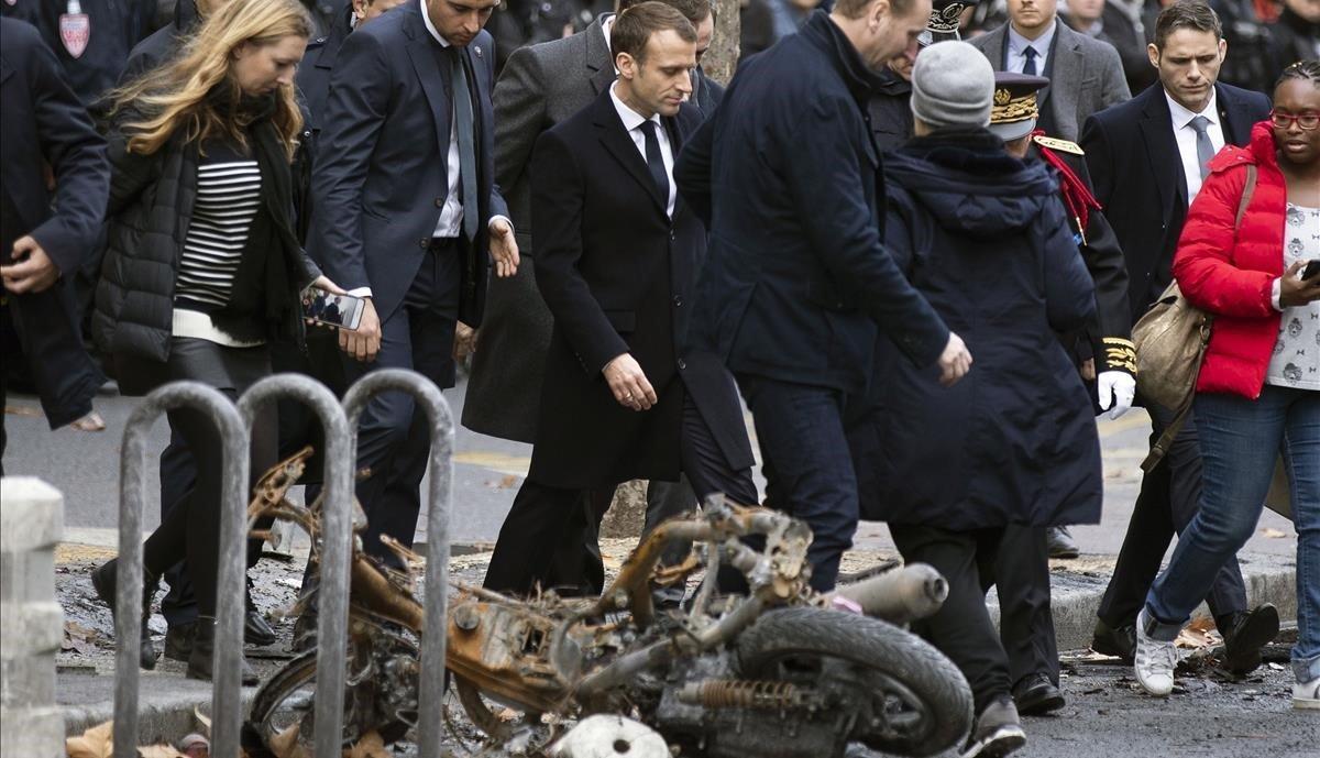 Emmanuel Macron pasa cerca de una motocicleta incendiada en los disturbios del pasado 1 de diciembre.