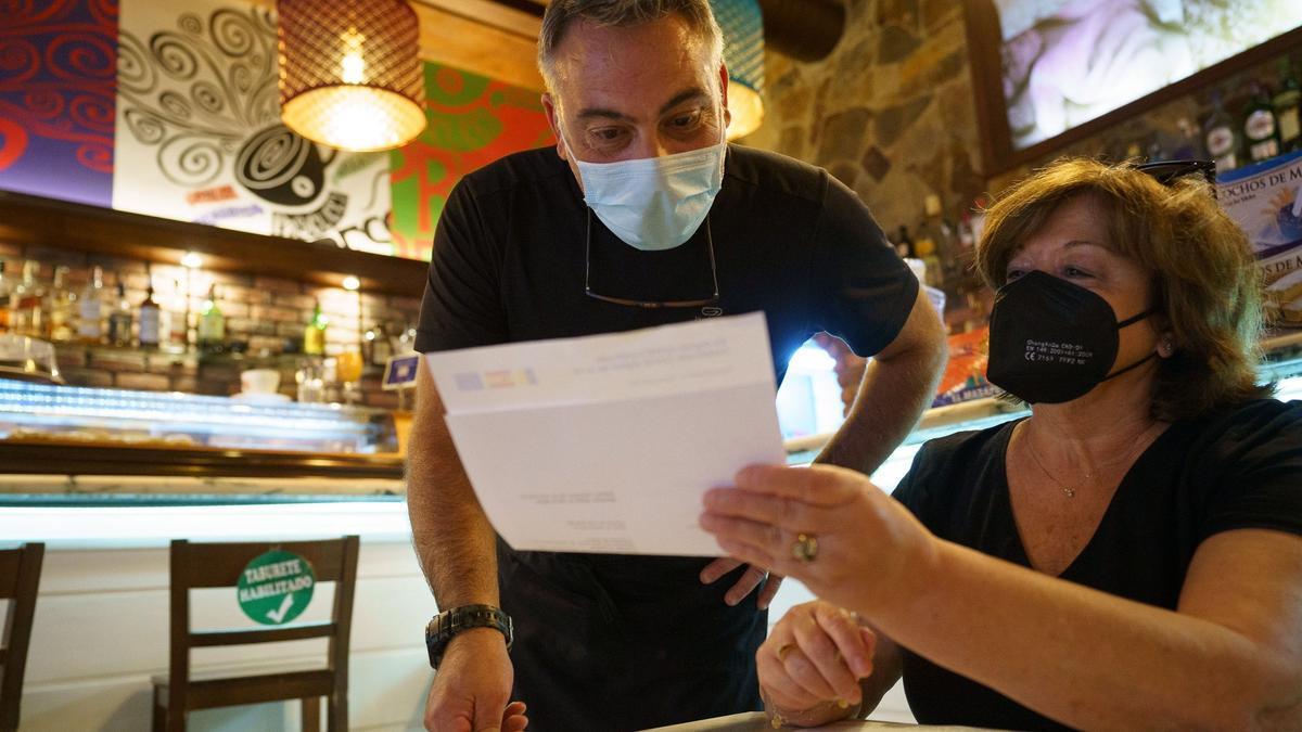 Personal de una cafetería de Santa Cruz de Tenerife, comprueba el certificado Covid de una clienta
