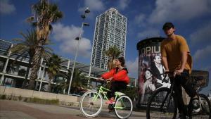 Dos ciclistas sin mascarilla circulan frente al Hotel Arts, hace unos días.