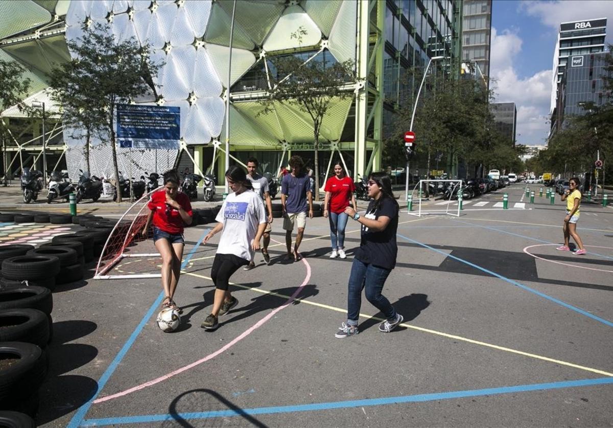 Los estudiantes de arquitectura trabajan en la zona de juegos infantiles en la 'superilla'de Poblenou, entre Roc de Boronat y Sancho de Ávila.
