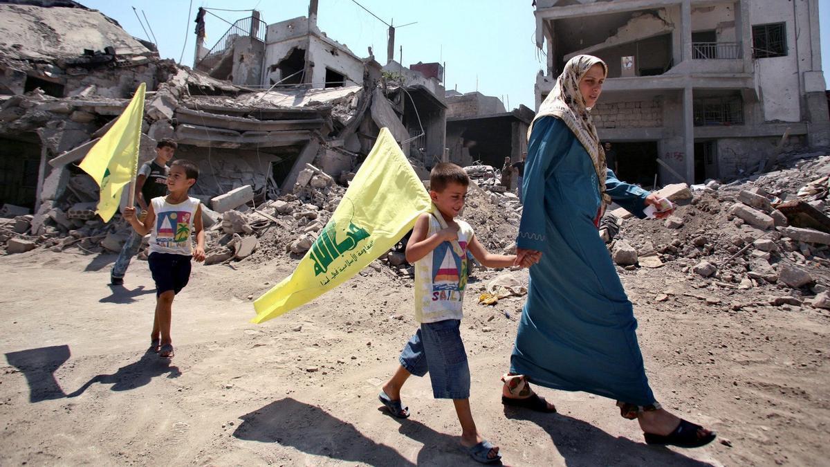 Una mujer libanesa y sus hijos, sosteniendo banderas de Hezbolá, pasan junto a los escombros de las casas dañadas durante el reciente conflicto entre Israel y Hezbolá en el Líbano en la aldea de Saddikine, en el sur del Líbano, el 22 de agosto de 2006.